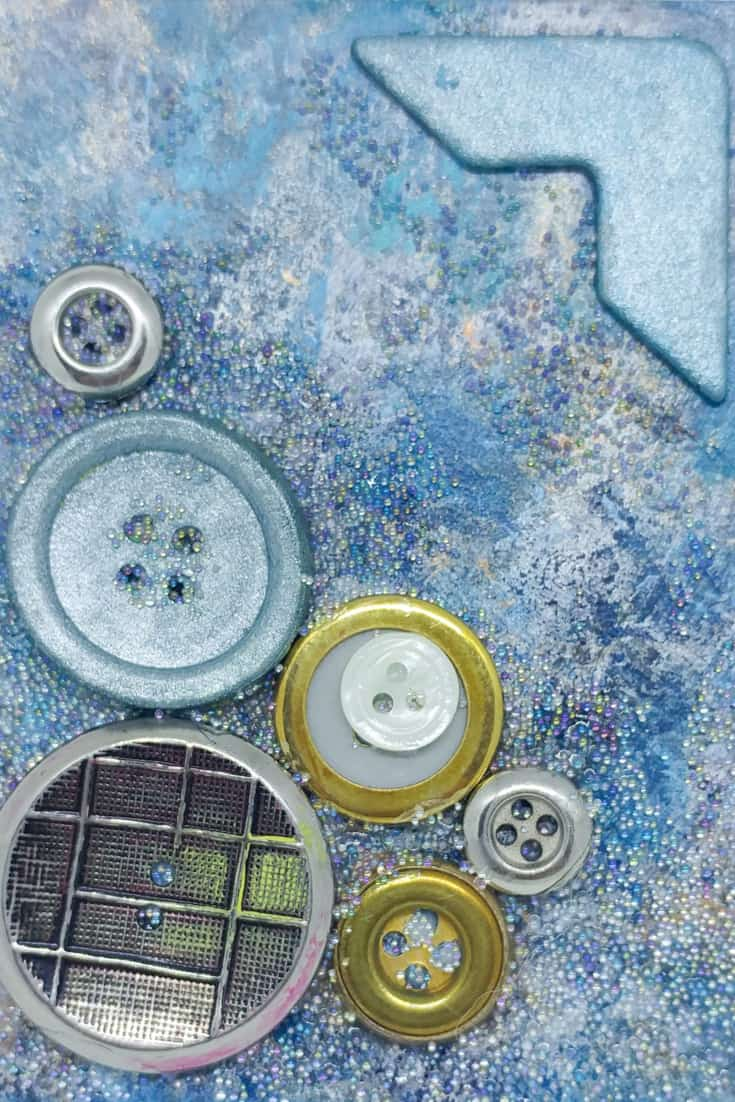 In this lesson, check out how I use simple buttons in mixed media art, based on a Book of Backgrounds page.